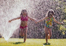 Girls Running Through Sprinkler